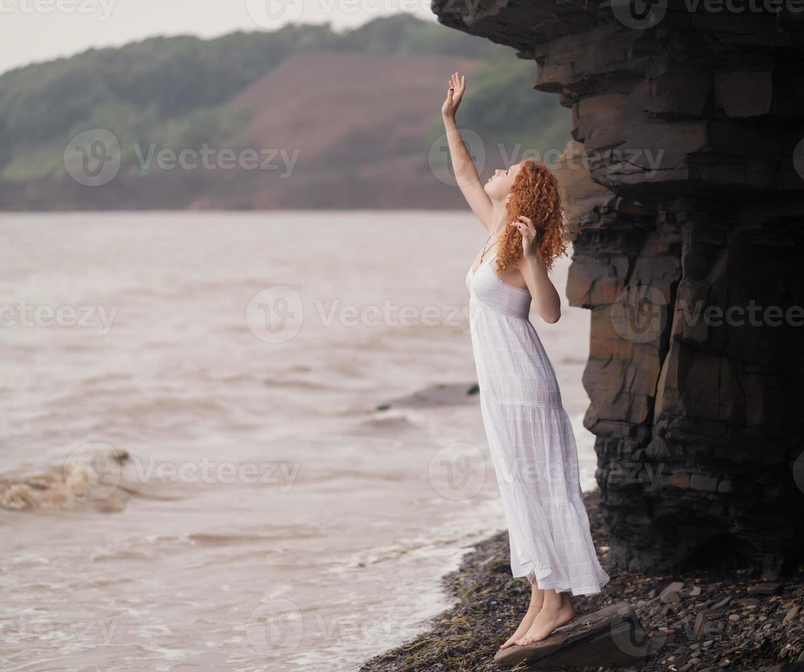 Woman in white dress standing on beach. photo