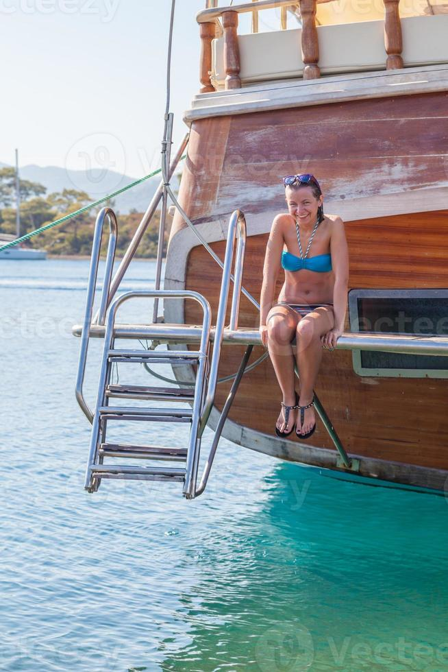 Girl sitting on board the ship and laughs photo