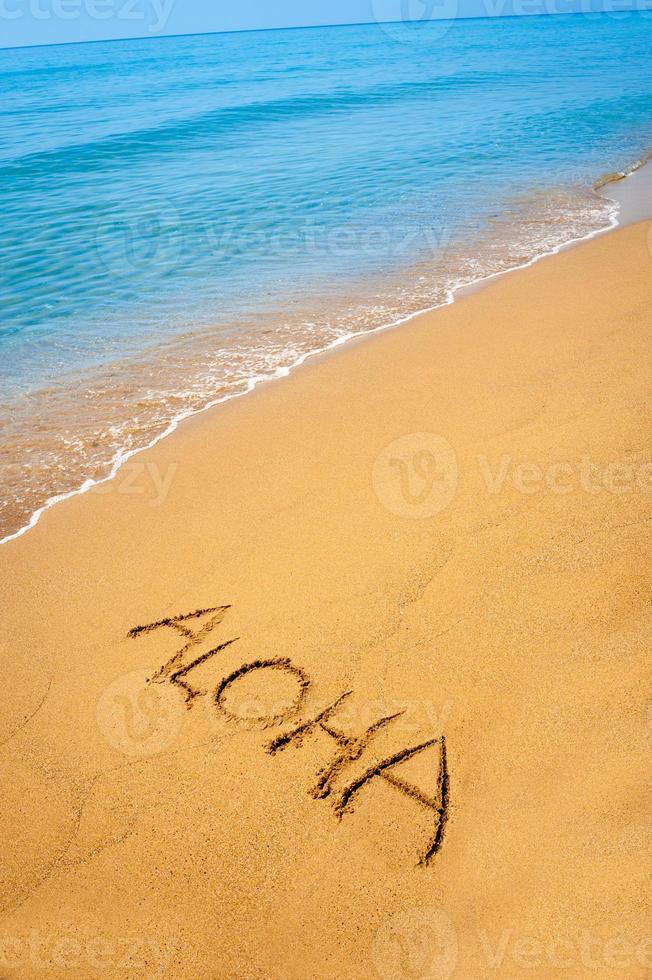Sign aloha written in sand, on tropical beach photo