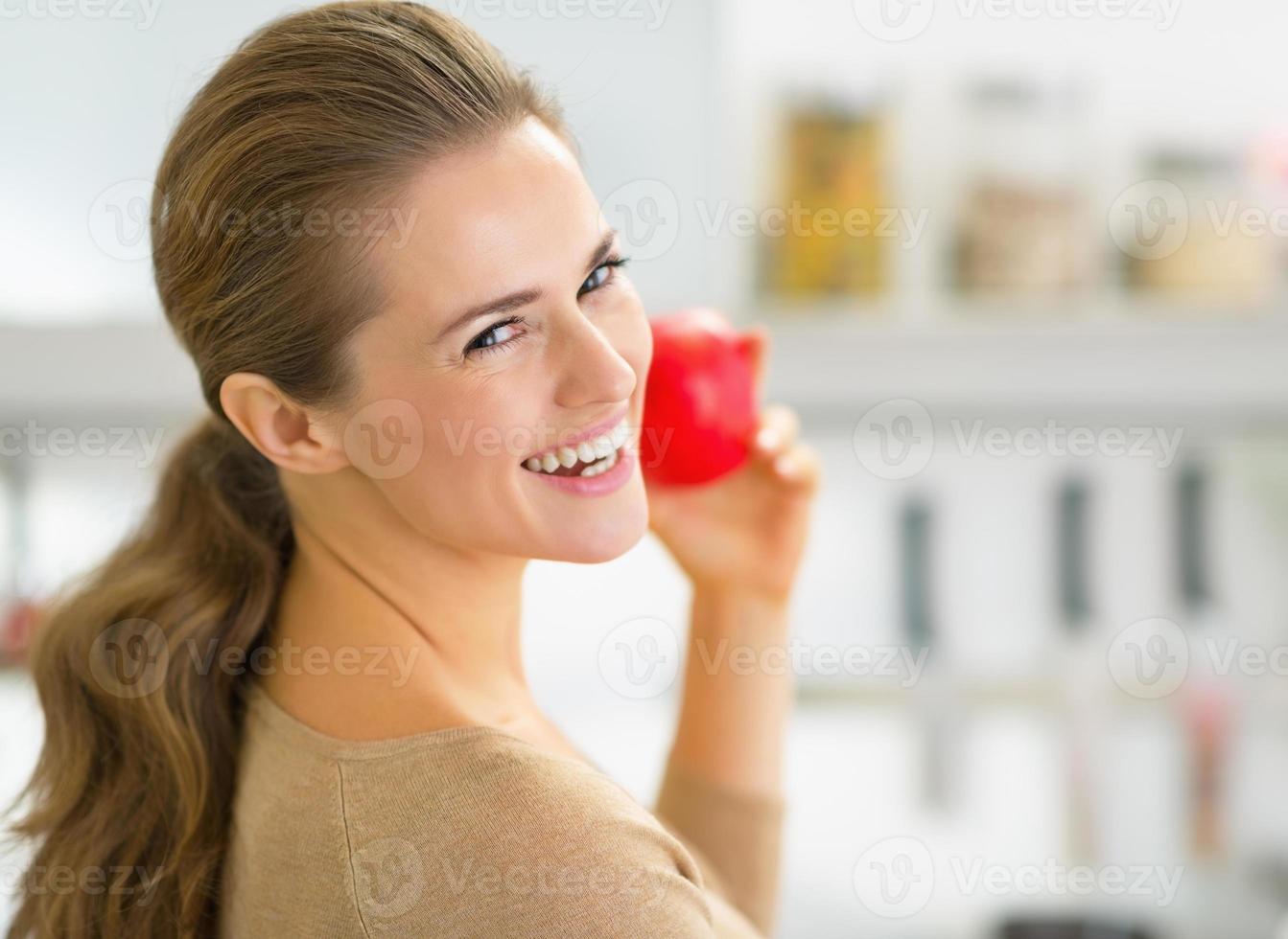 Retrato de mujer joven feliz manzana en cocina foto