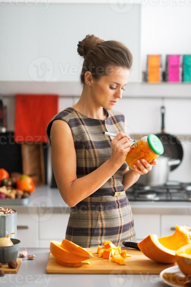 joven ama de casa firma jarra de calabaza en escabeche en la cocina foto