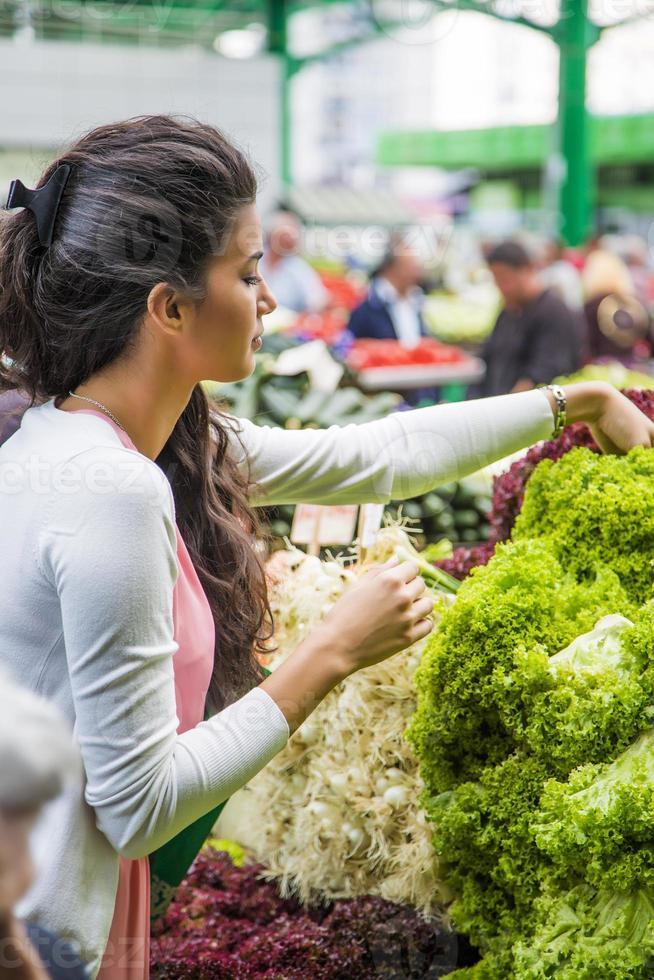 Bastante joven mujer comprando verduras en el mercado foto