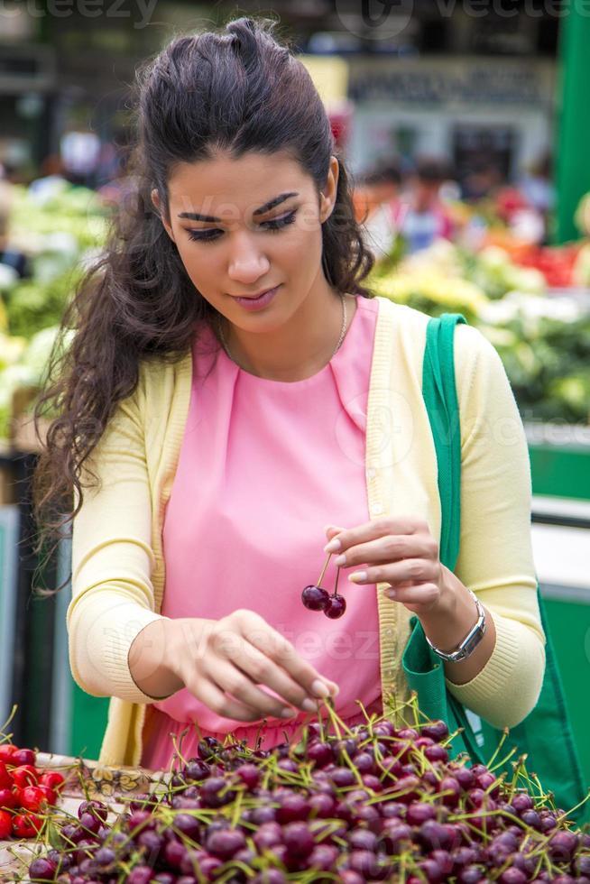 mujer joven comprando cerezas foto