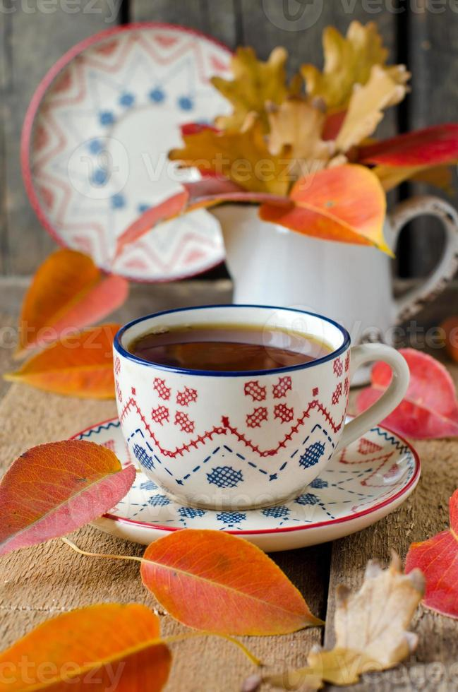 cup of tea on the table with autumn leaves photo