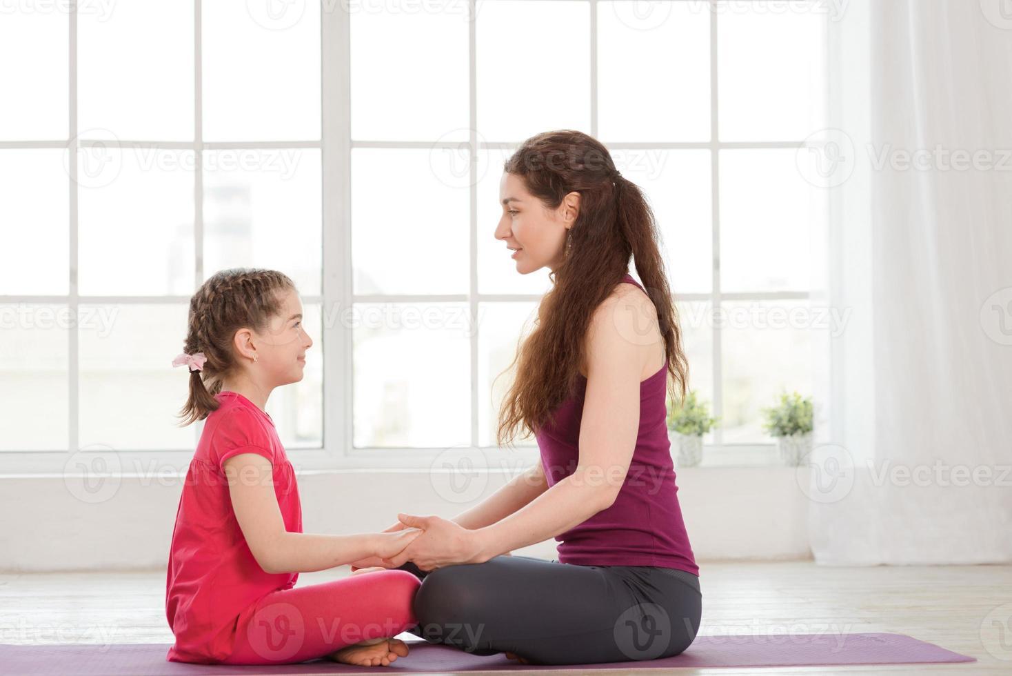 joven madre e hija haciendo ejercicio de yoga foto