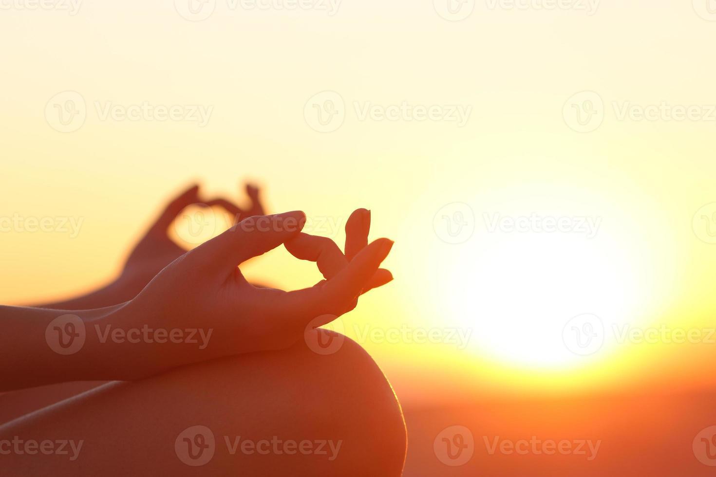manos de mujer ejercicio de yoga al atardecer foto