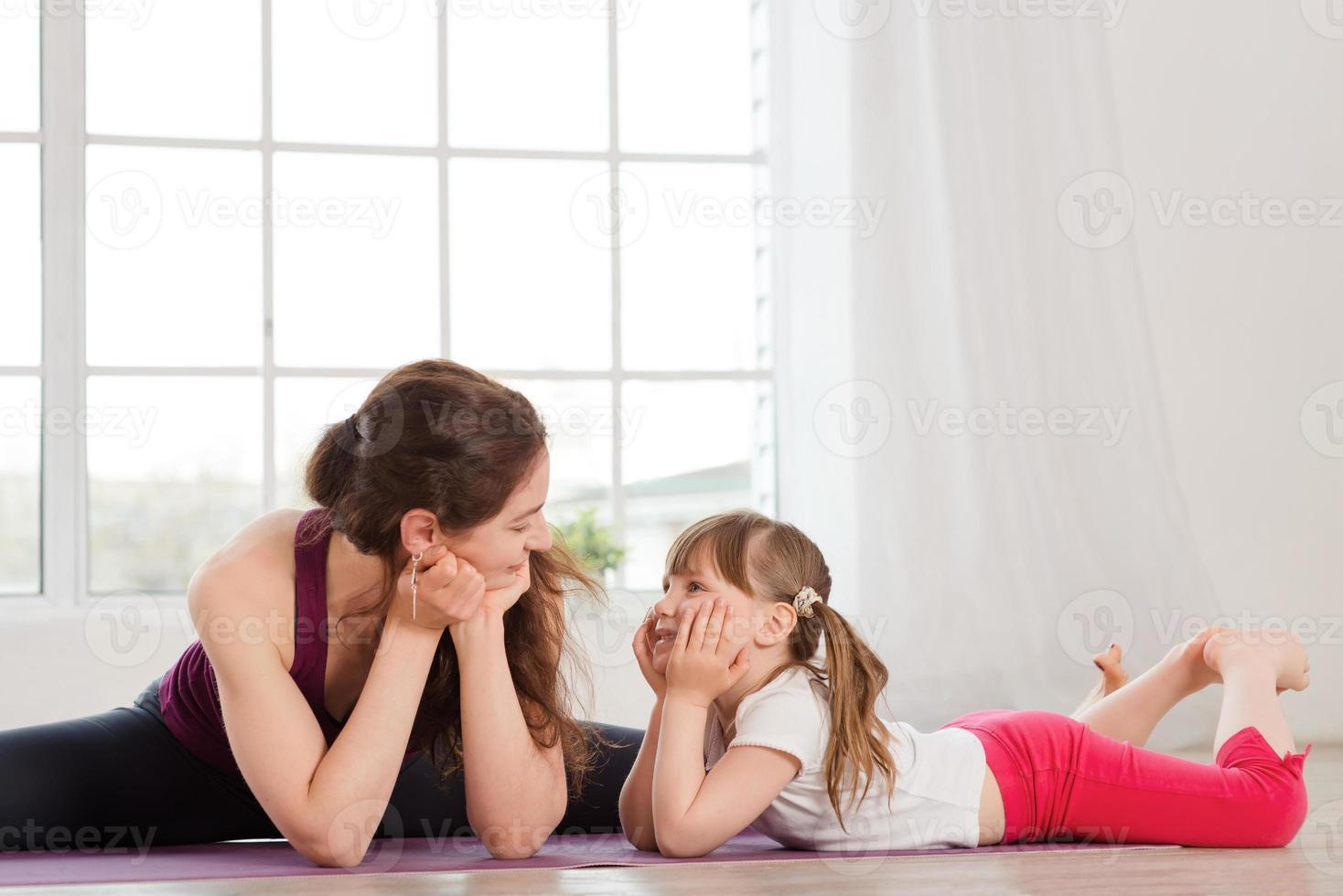 joven madre hablando con su hija durante el ejercicio de yoga foto