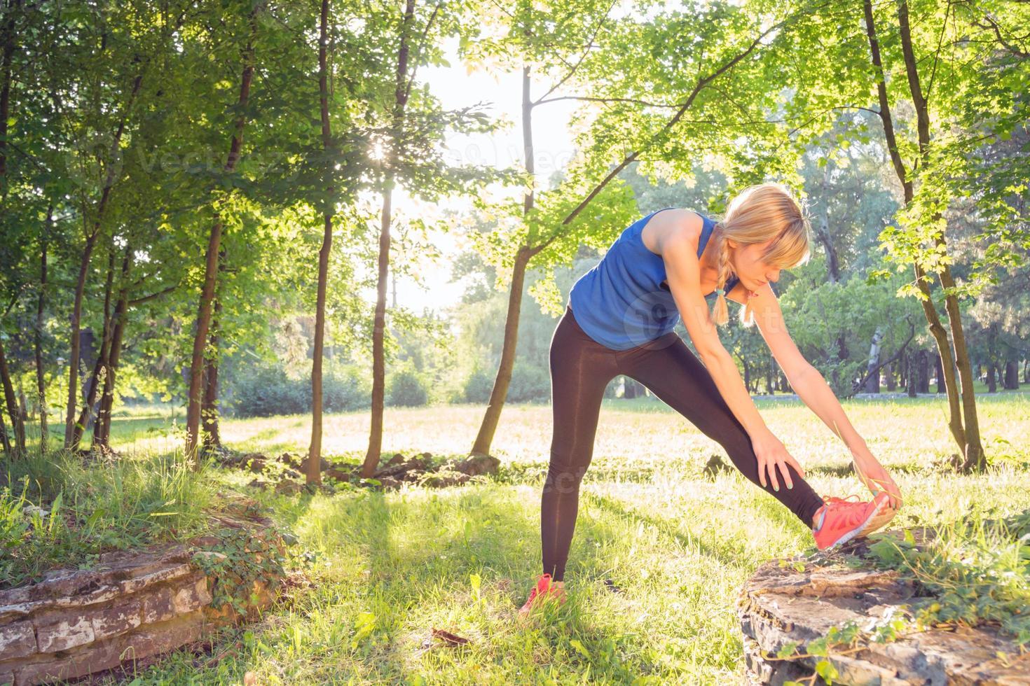estiramientos después del ejercicio / trotar en el parque. foto