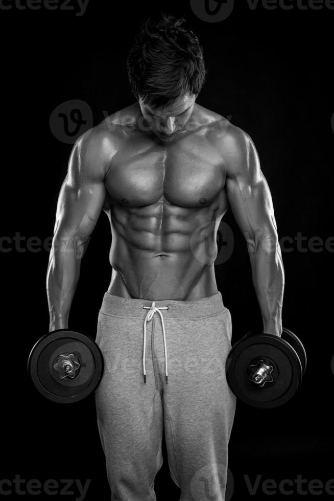 Muscular bodybuilder guy doing exercises with dumbbells photo