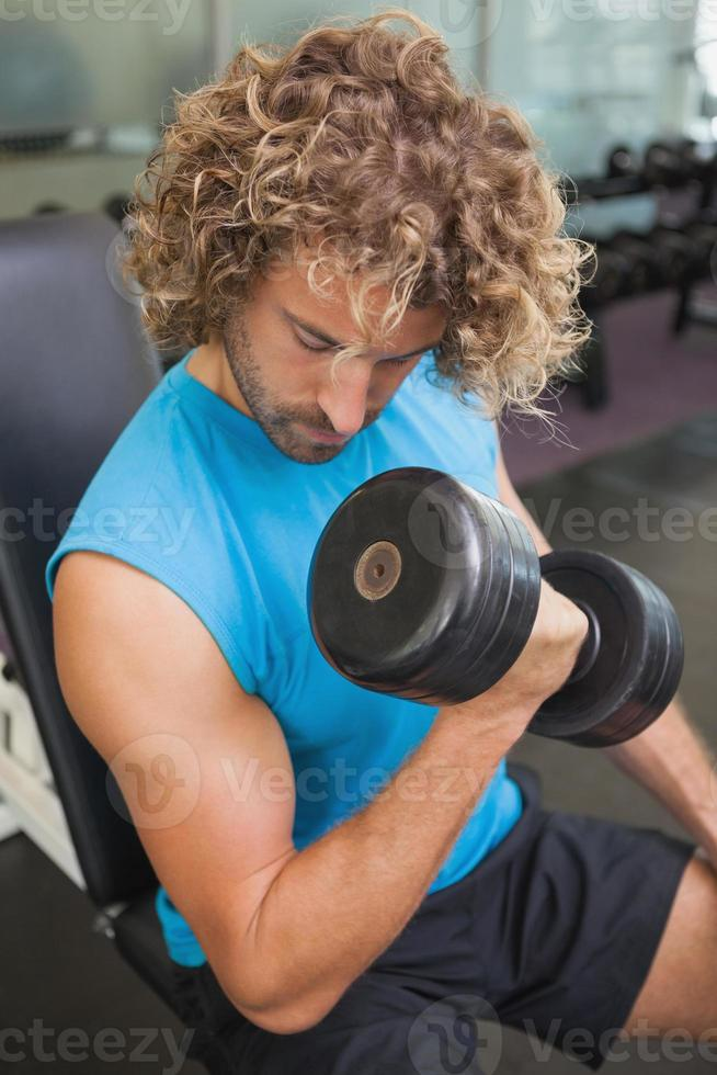 Handsome man exercising with dumbbell in gym photo