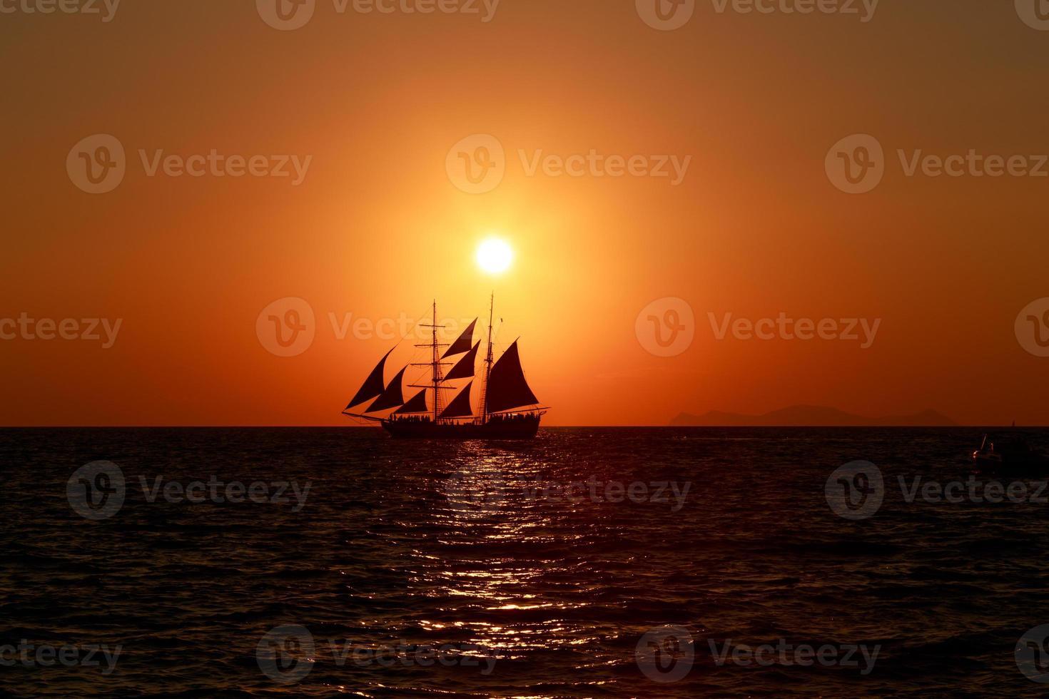 La puesta de sol sobre un velero en santorini. foto