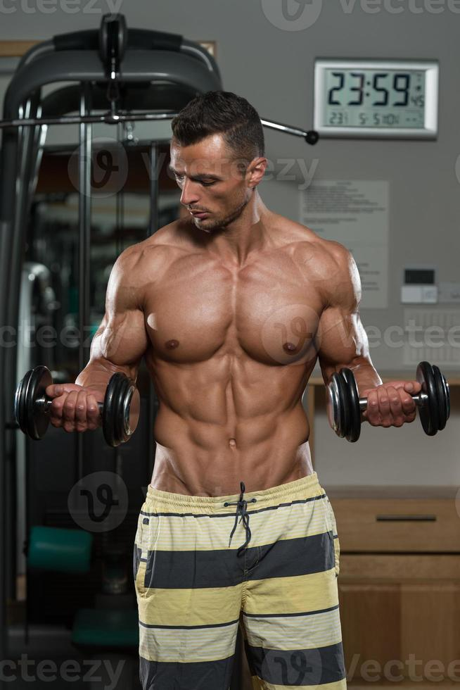 Young Man Doing Exercise For Biceps photo
