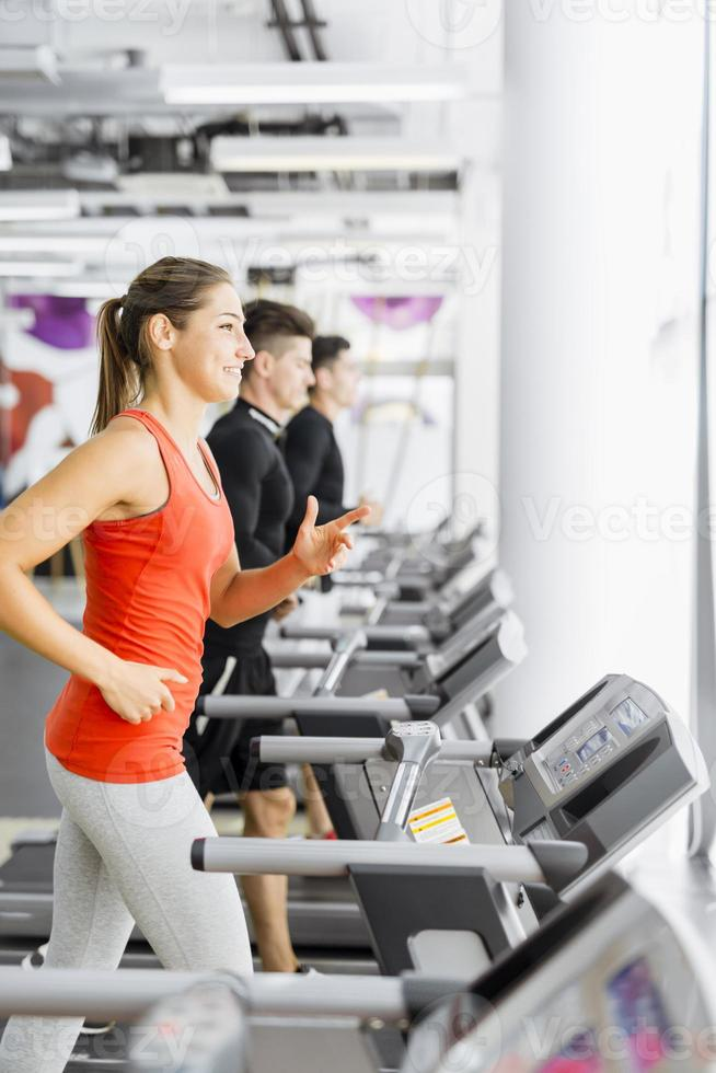 Group of young people using treadmills in a gym photo