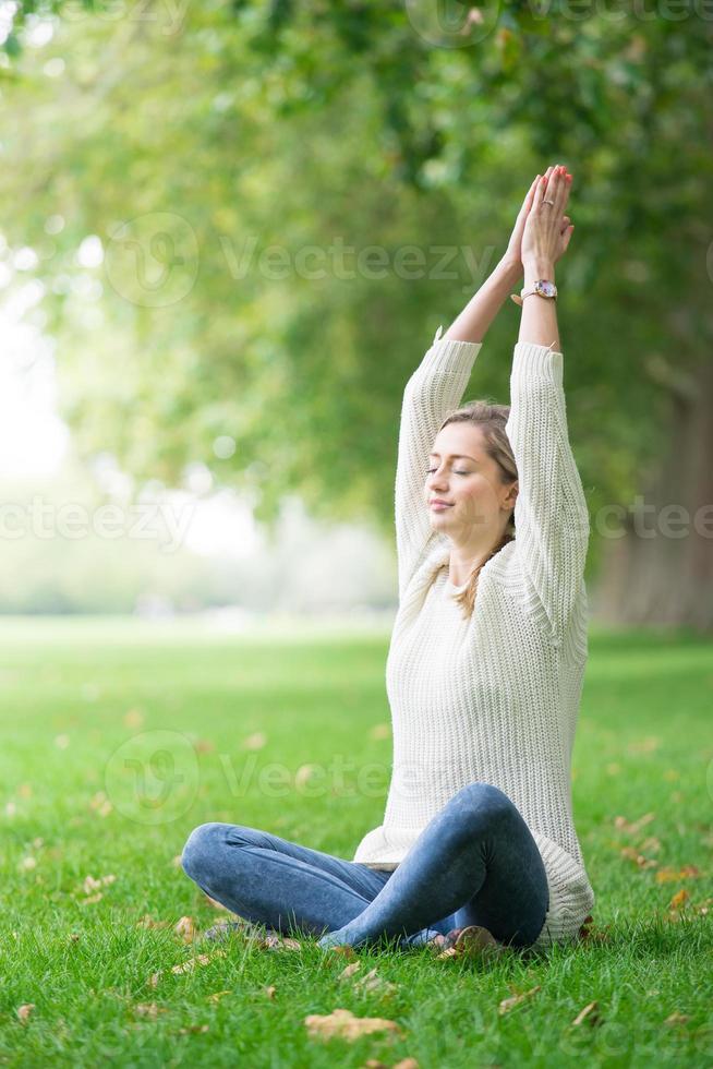 mujer joven meditando y yoga en un parque foto