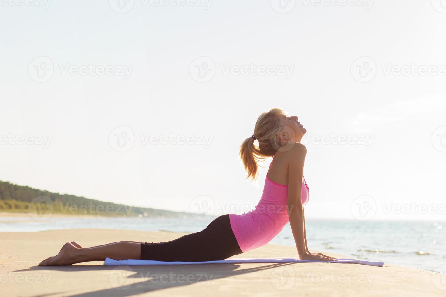 joven sana y en forma practicando yoga en la playa foto