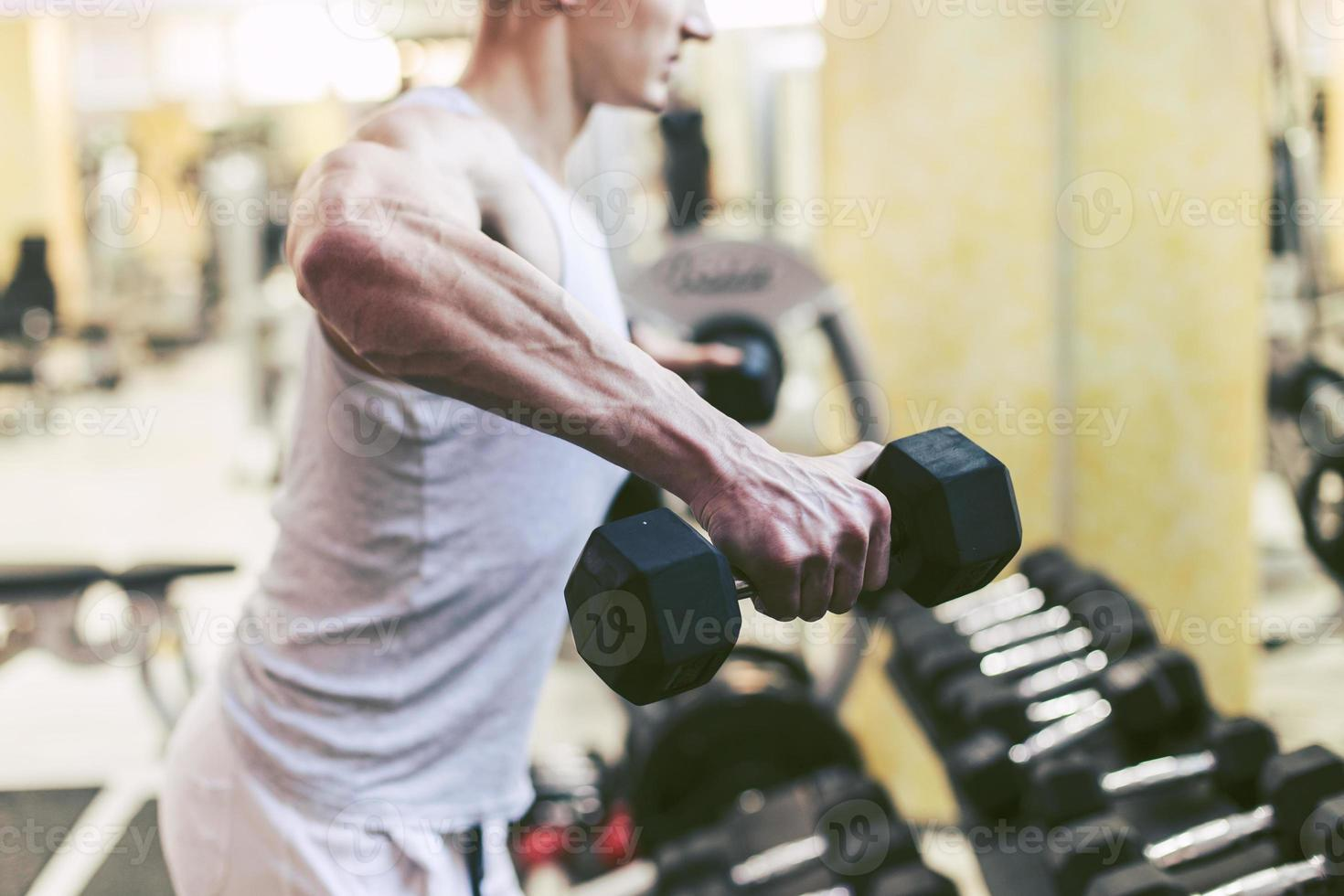 Muscular Bodybuilder Doing Exercises with Dumbbells in Gym photo