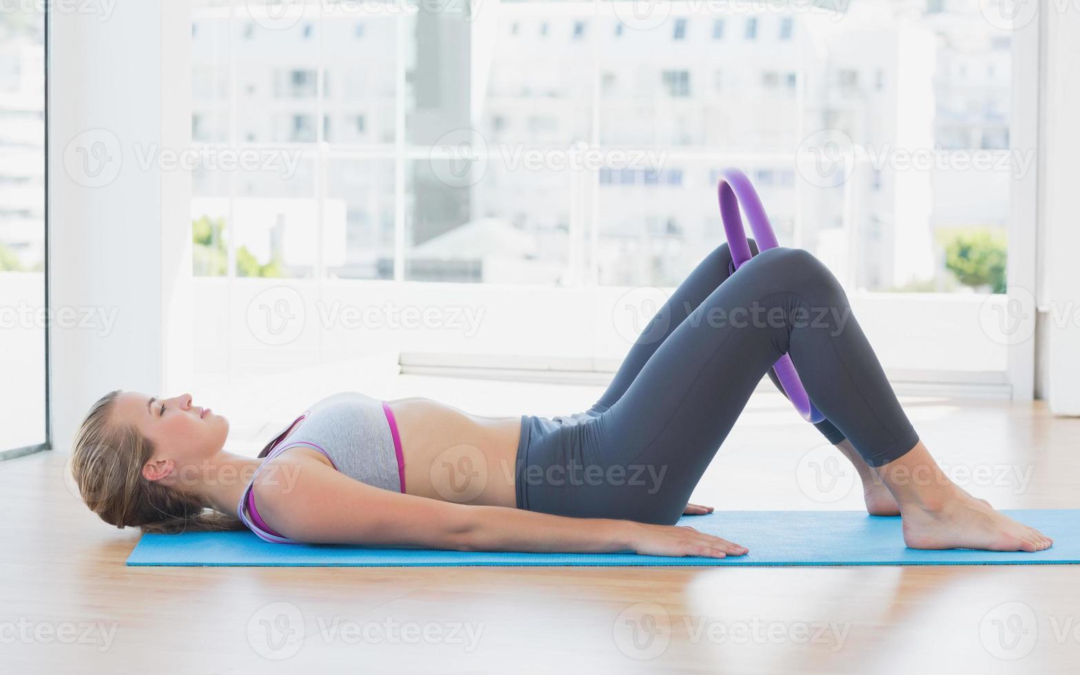 mujer deportiva con anillo de ejercicio en gimnasio foto