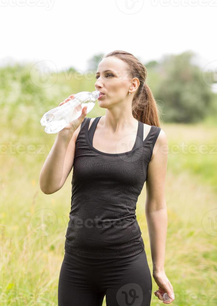 Young woman drinks water after making sport exercises photo