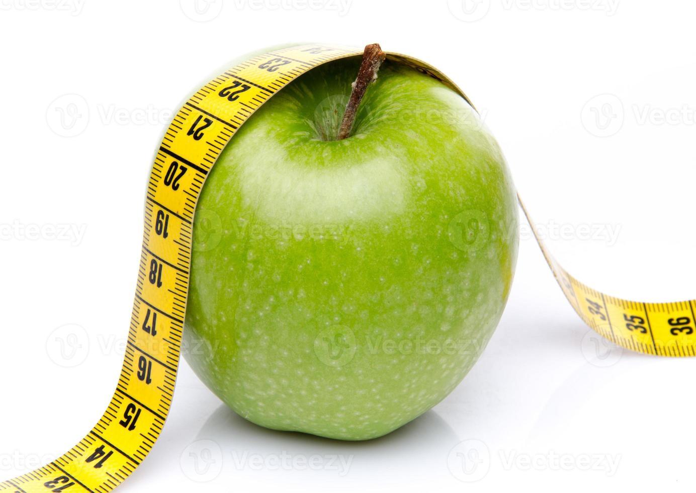 cinta métrica en una manzana verde foto
