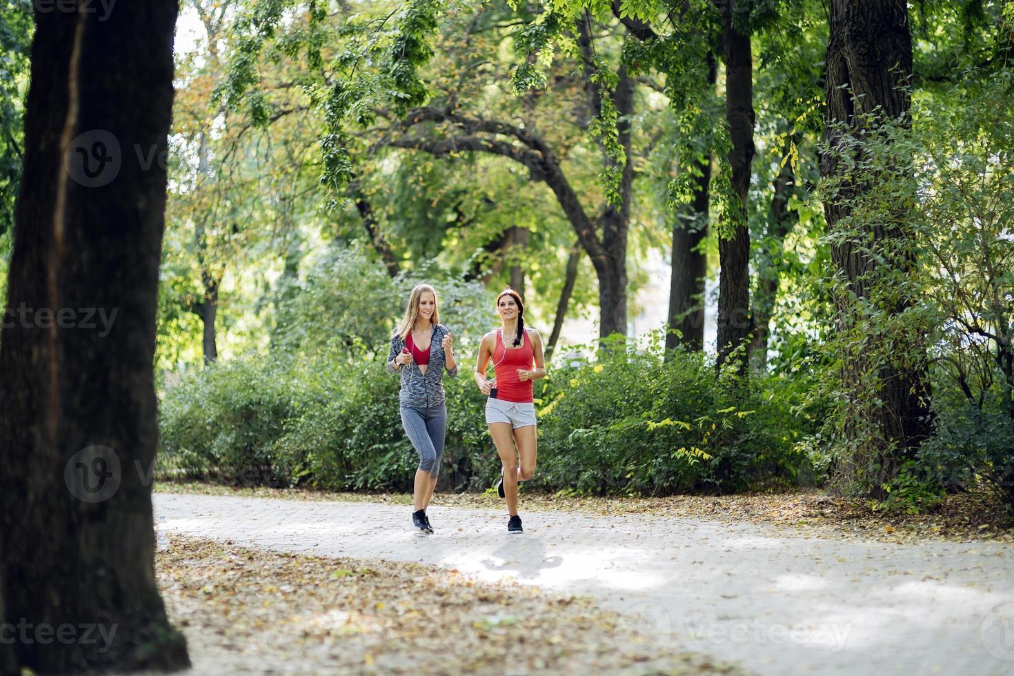 Two beautiful women jogging in park photo