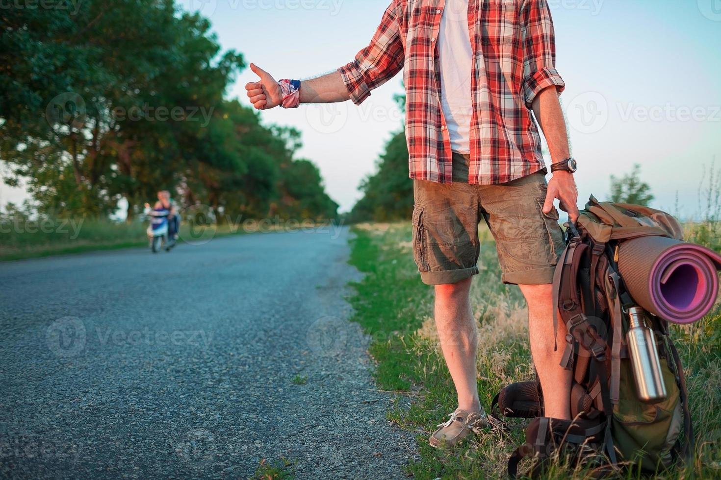 joven turista caucásico haciendo autostop a lo largo de una carretera foto