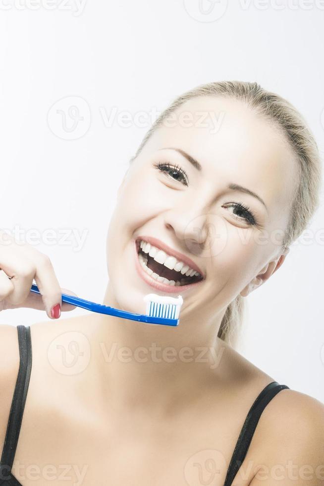sonriente mujer caucásica con cepillo de dientes contra blanco foto