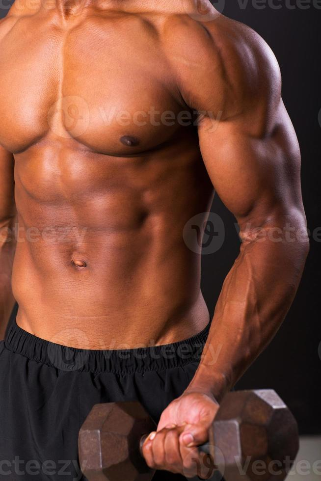 young african man working out with dumbbells photo