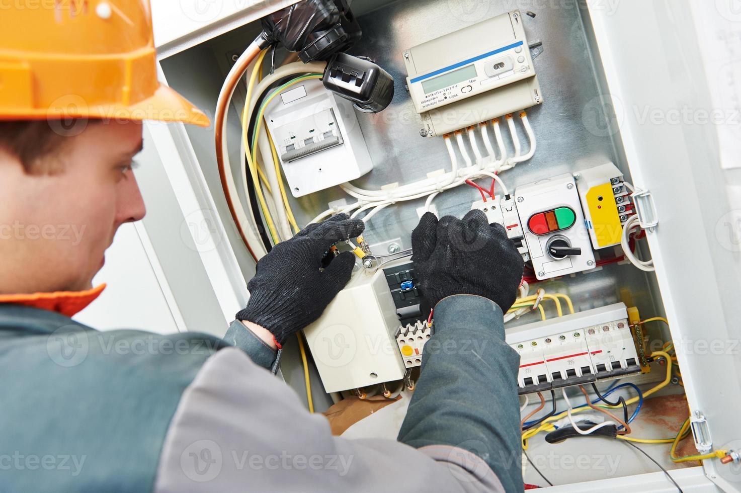 electricista caucásico con sombrero naranja fijación caja de cables foto