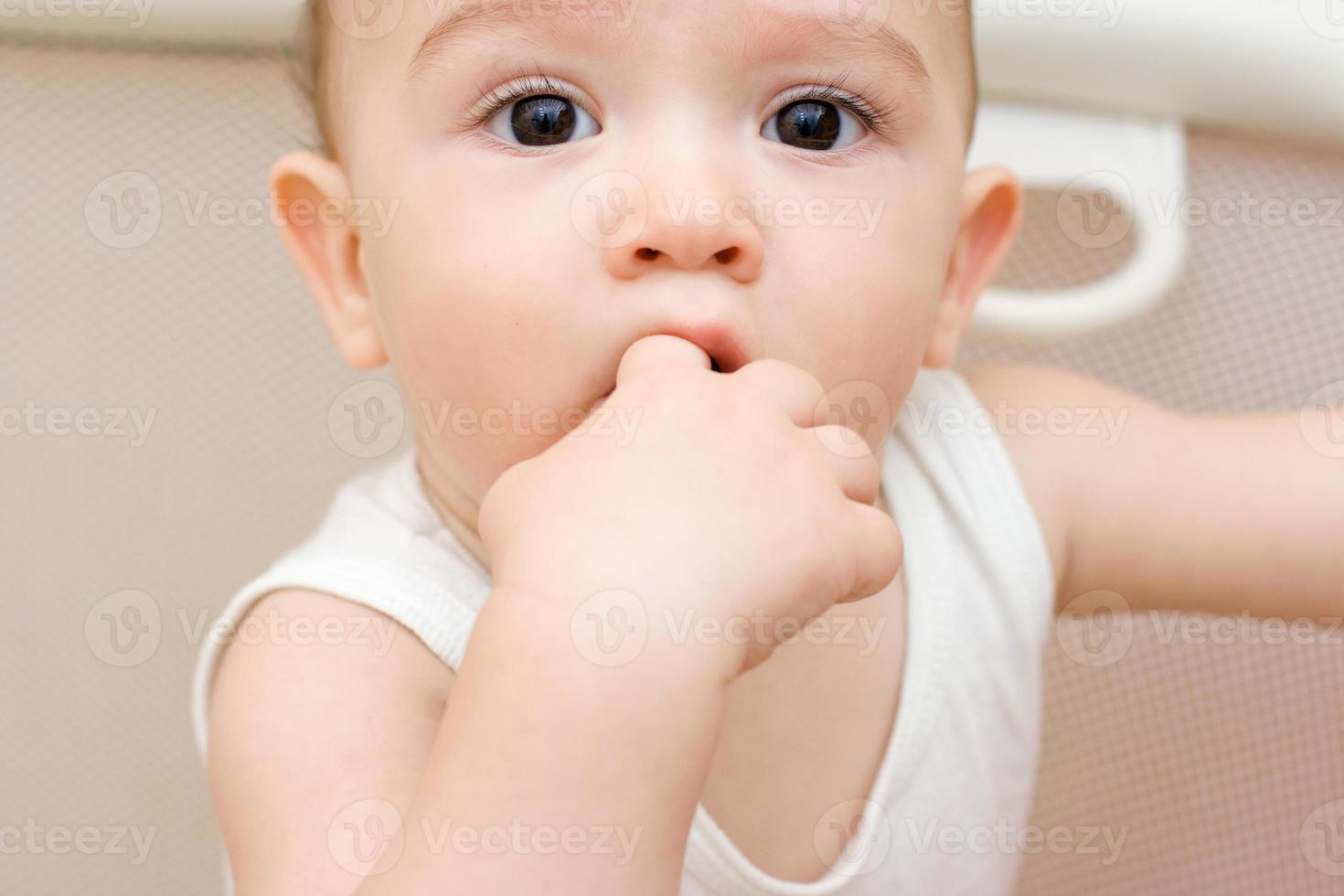 Fun caucasian baby with finger in his mouth photo