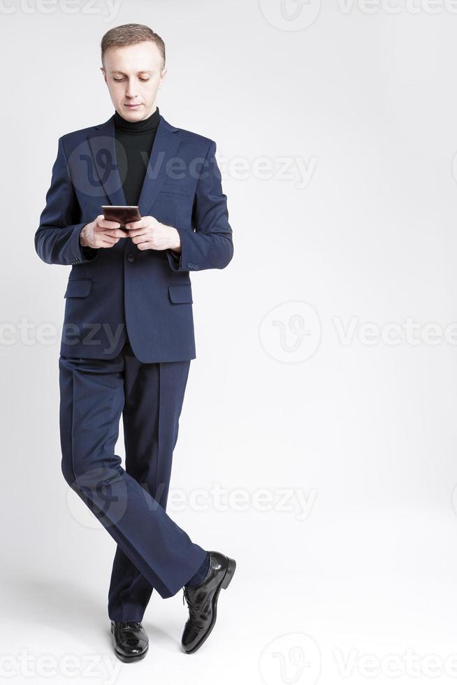 Retrato de cuerpo entero del empresario caucásico en elegante suite azul foto