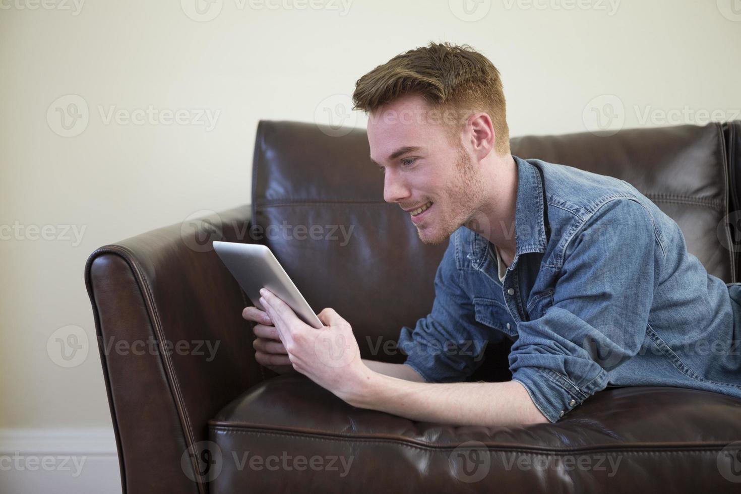Hombre caucásico con tableta digital en casa en el sofá. foto