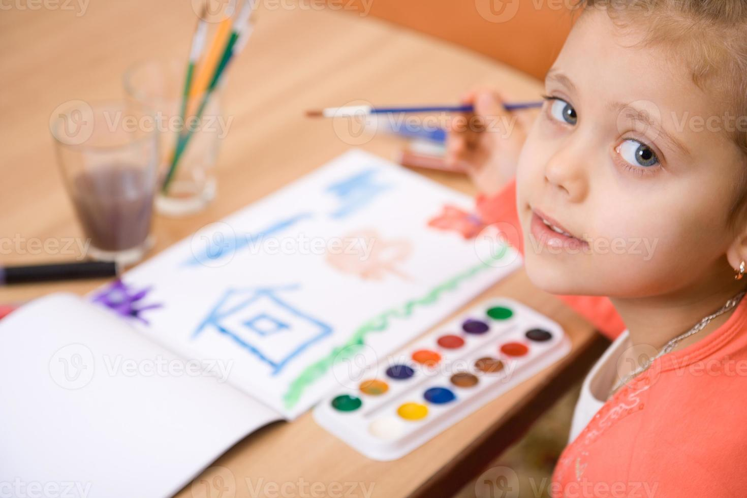 Pretty caucasian girl watercolor paint and look in camera photo