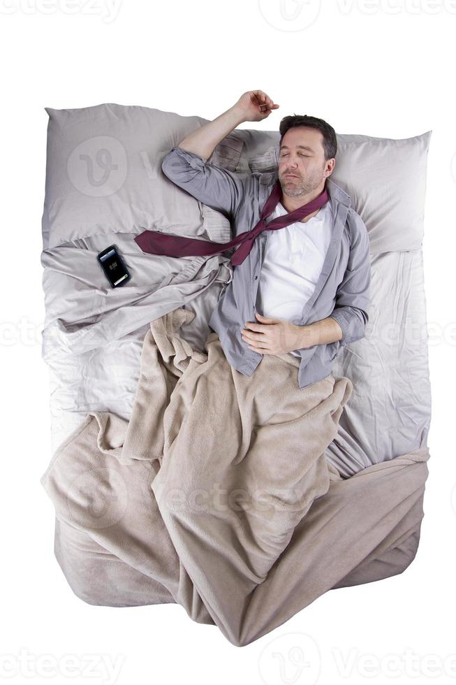 Caucasian Man Sleeping with Cell Phone Alarm in Bed photo