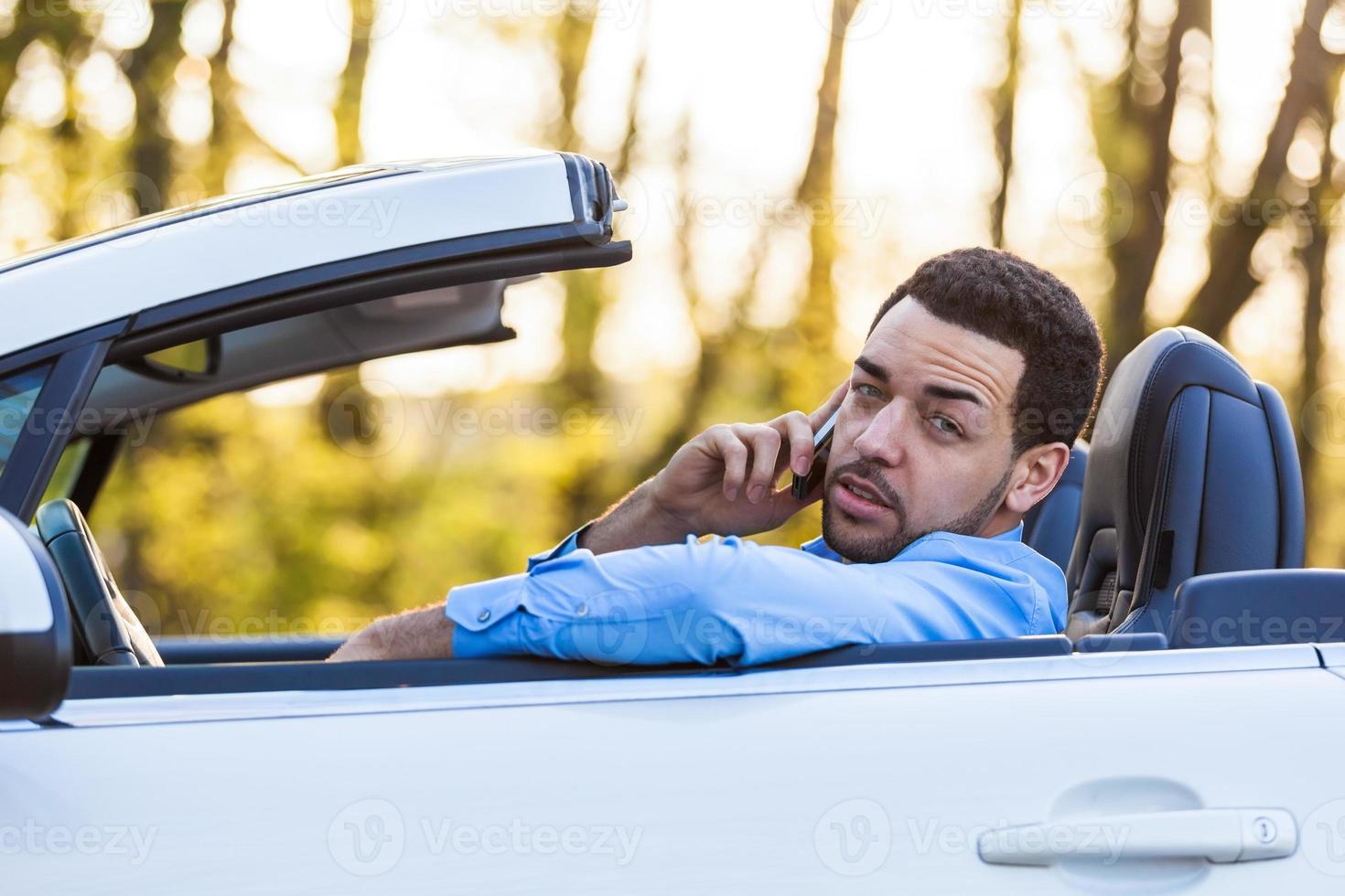joven conductor latinoamericano haciendo una llamada telefónica mientras conduce foto