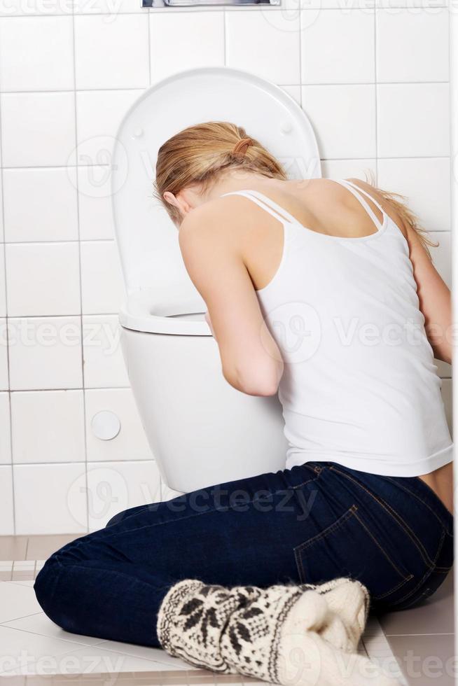 joven mujer caucásica está vomitando en el baño. foto