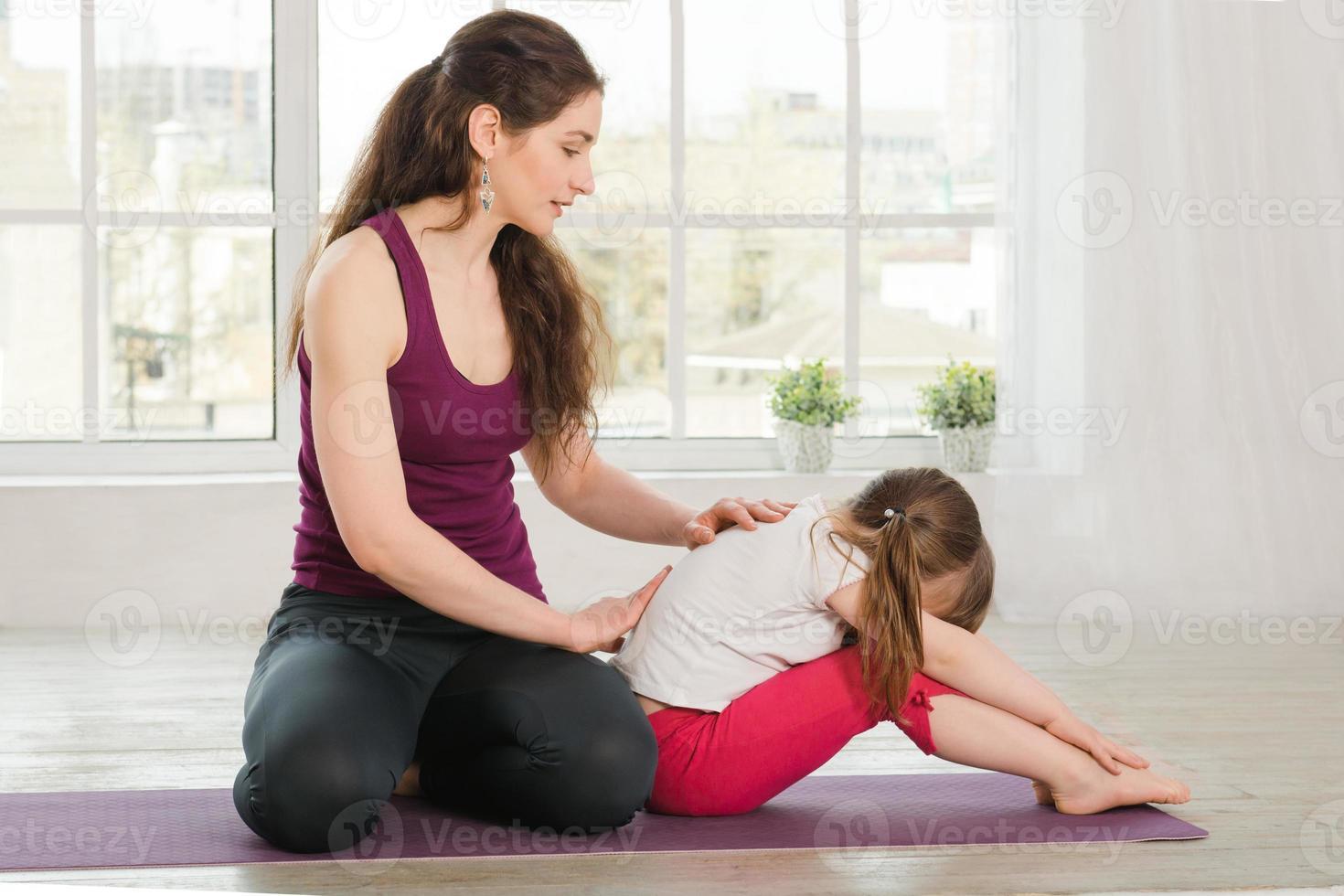 joven madre reconfortante hija durante el ejercicio de yoga foto