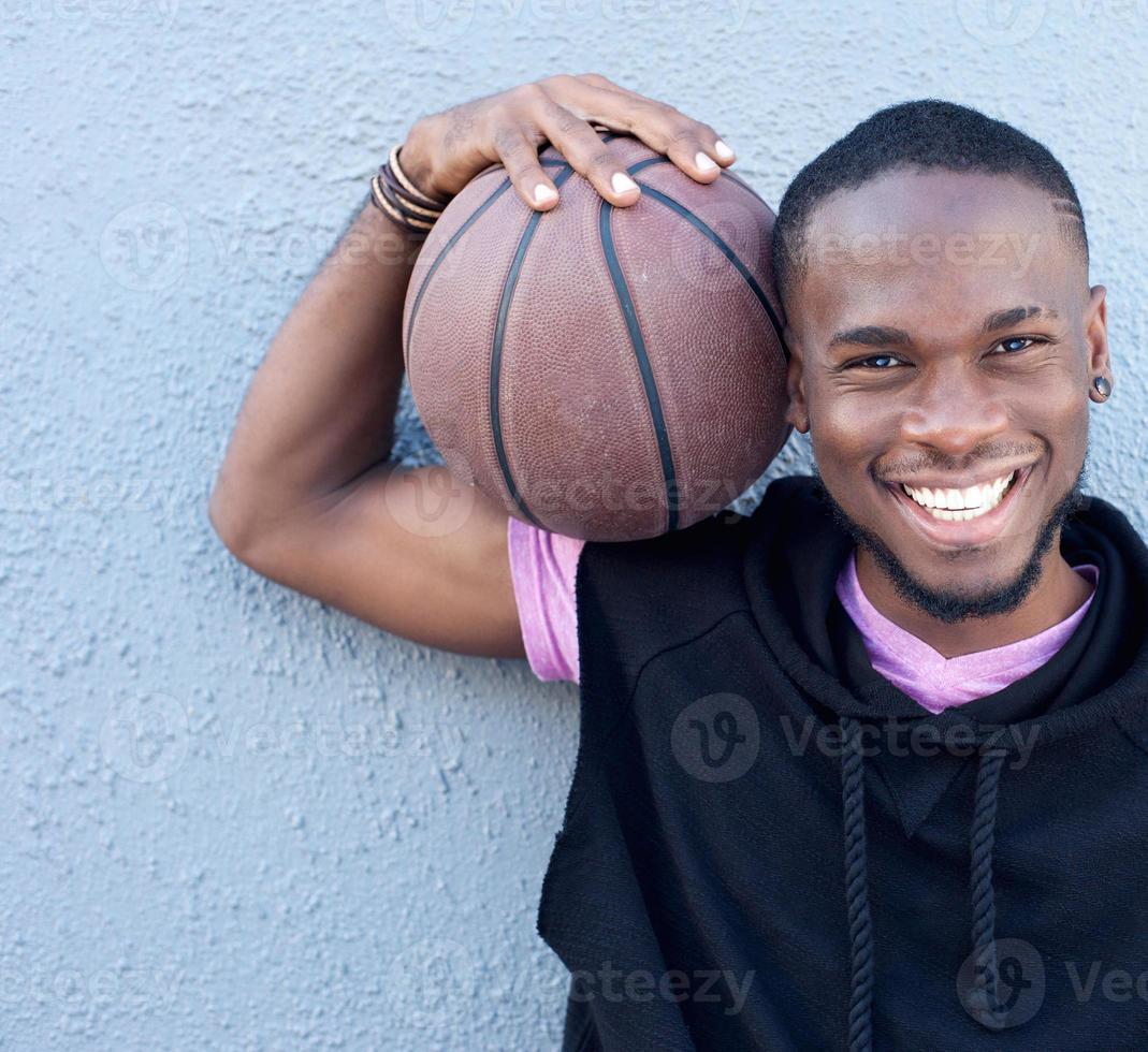 alegre hombre afroamericano sosteniendo baloncesto foto