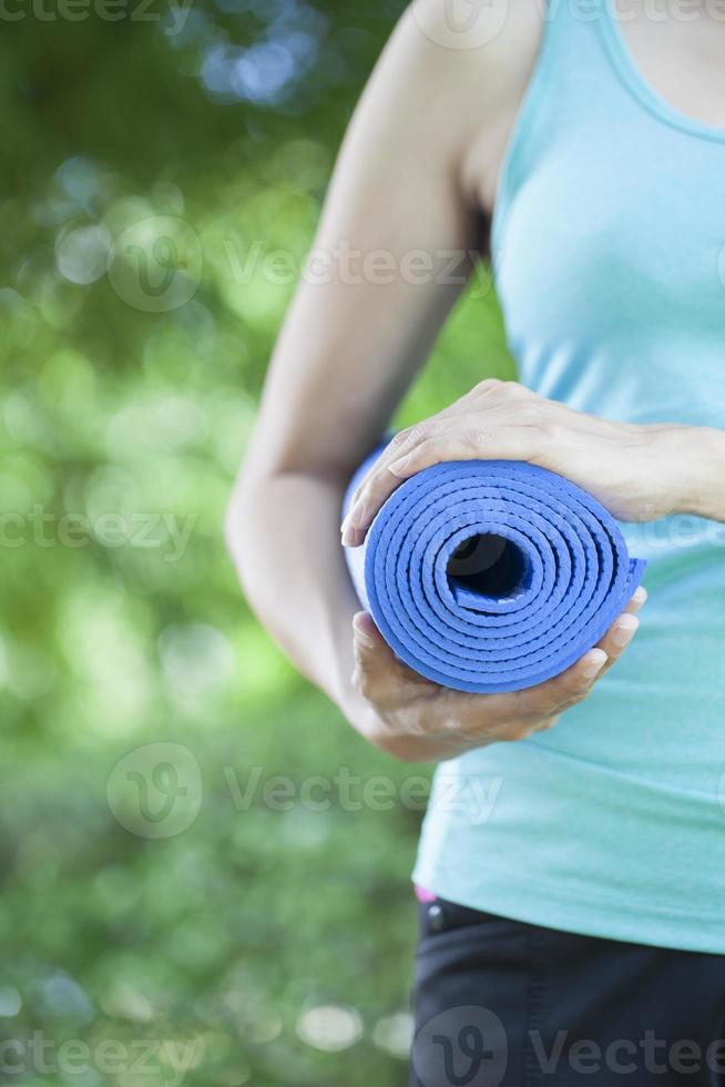 Young woman holding a yoga mat photo