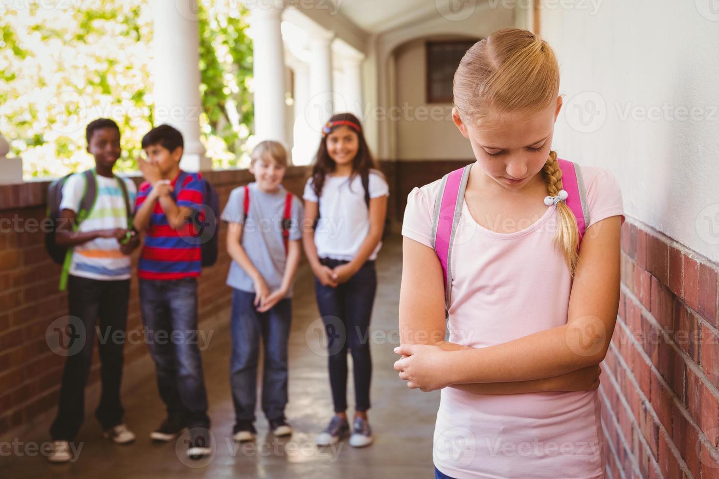 Triste colegiala con amigos en segundo plano en el pasillo de la escuela foto