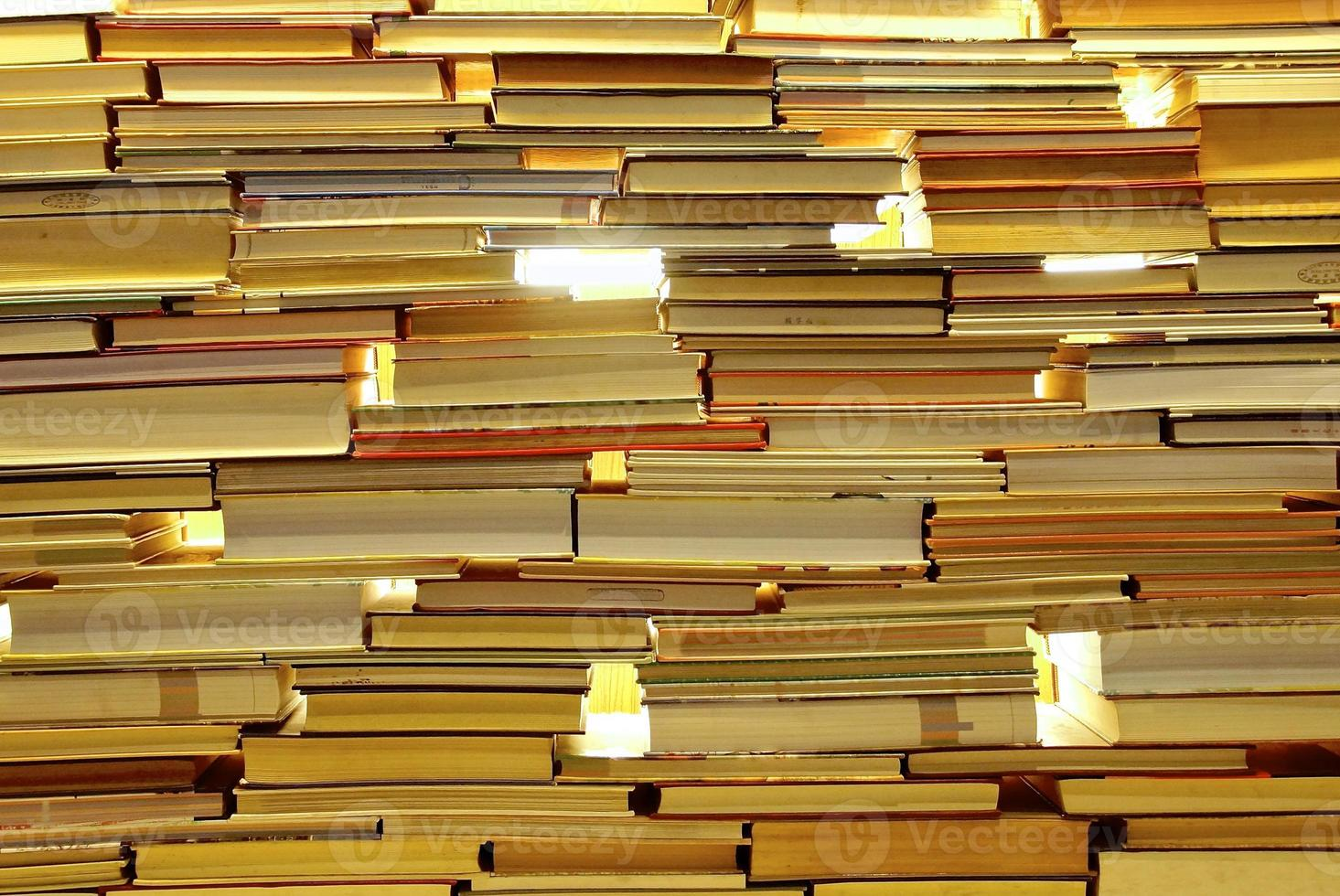 Stacks of books forming a wall with see through holes photo