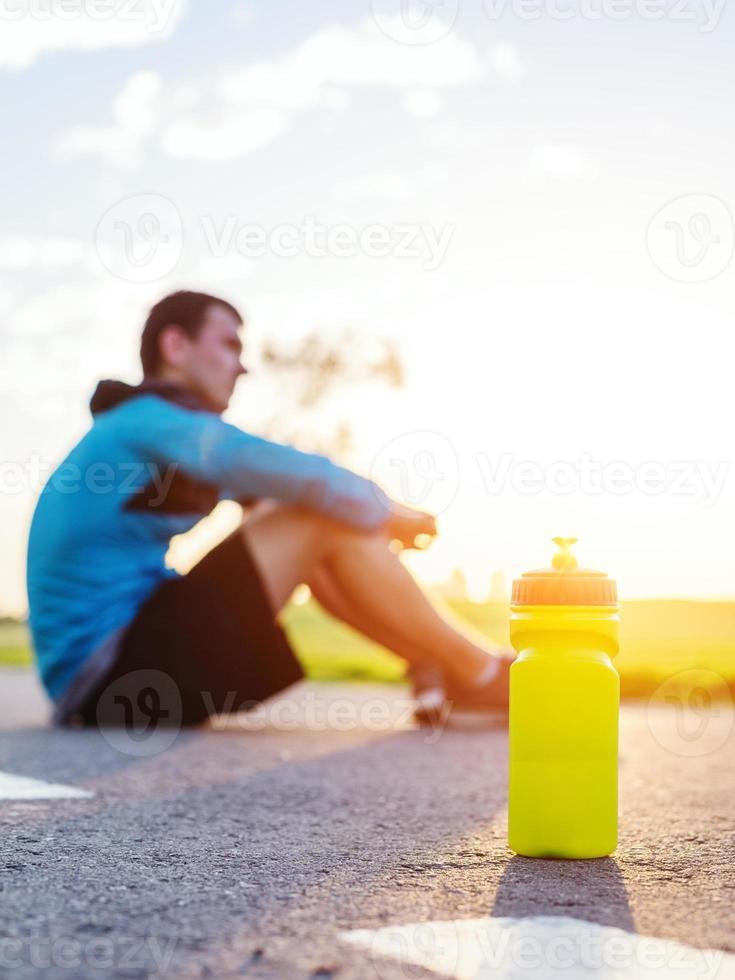 botella deportiva con agua y corredor foto