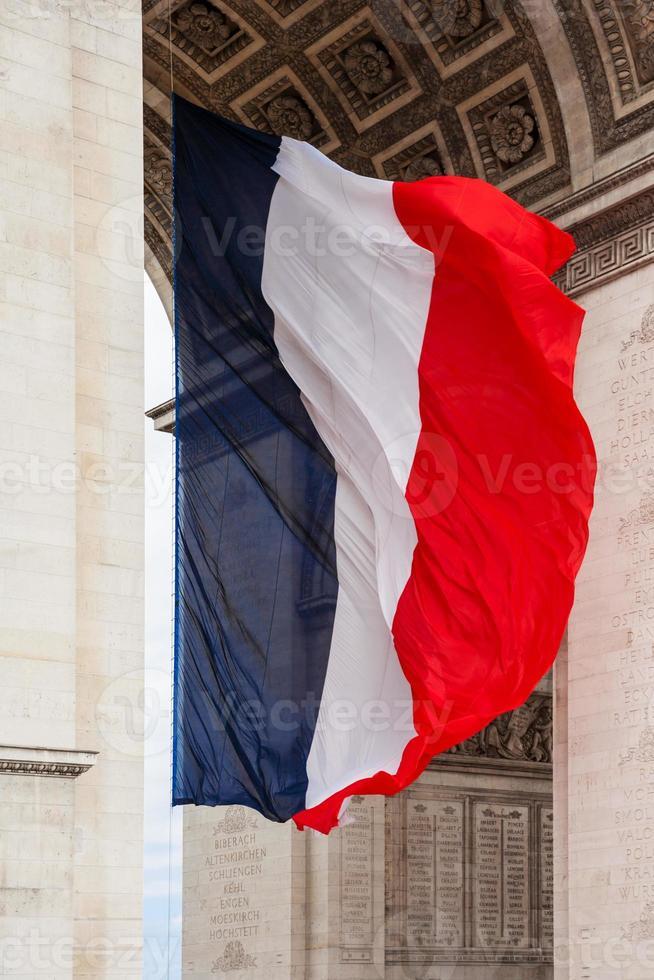 Bandera nacional de Francia con detalle de arco triunfal, París, Francia foto