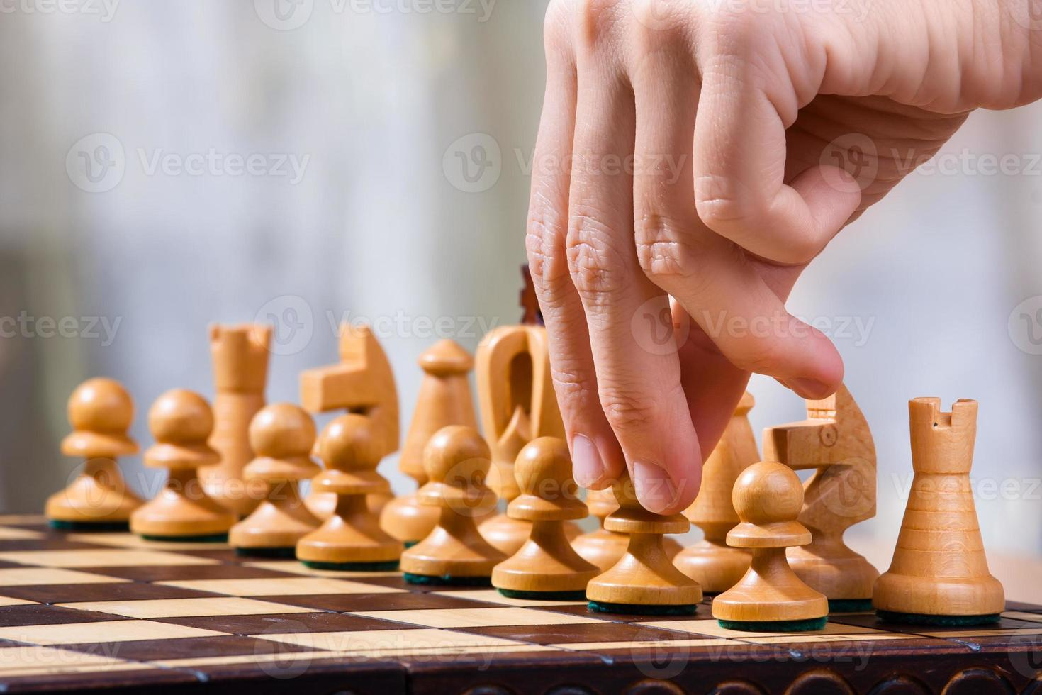hand of chess player with pawn photo