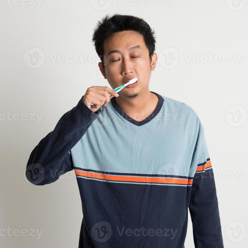 hombre asiático cepillarse los dientes foto