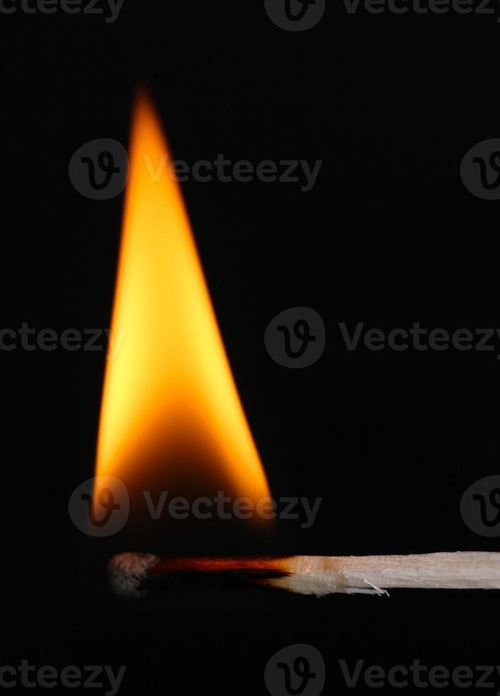 Burning match isolated on black photo