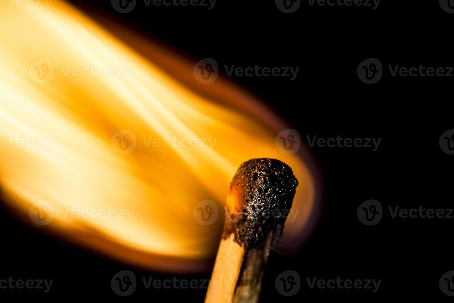 Close up burning matchstick on black background photo