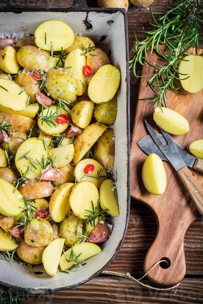 Preparing baked potatoes with herbs and garlic photo