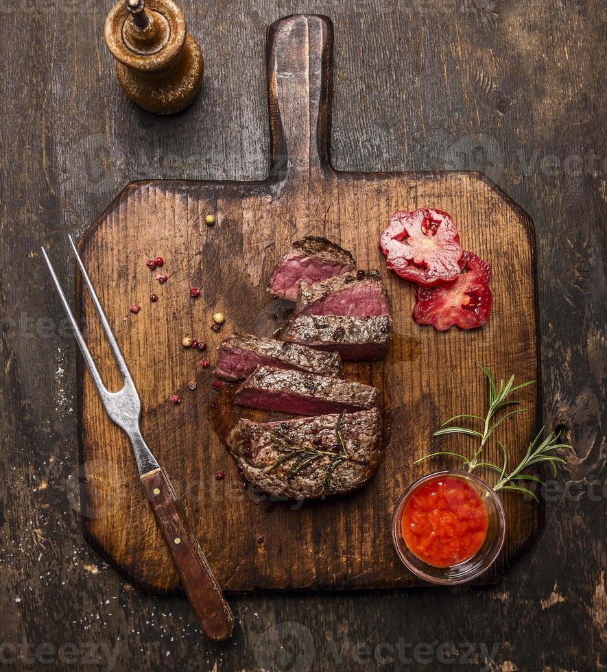 roasted  ribeye steak sliced on a cutting board photo