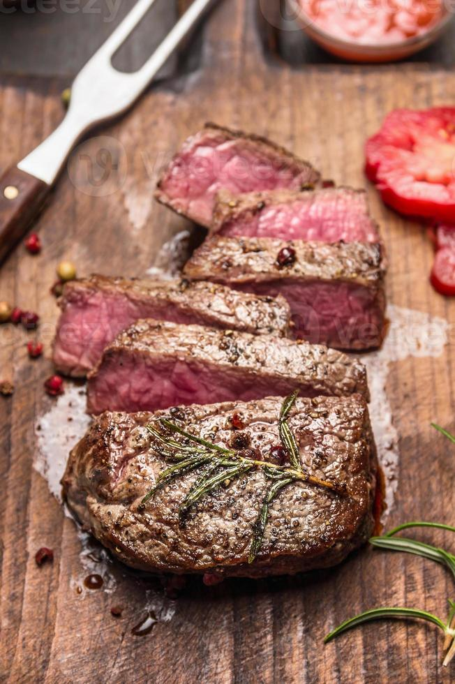 Medium rare roasted beef steak slices rustic wooden background photo