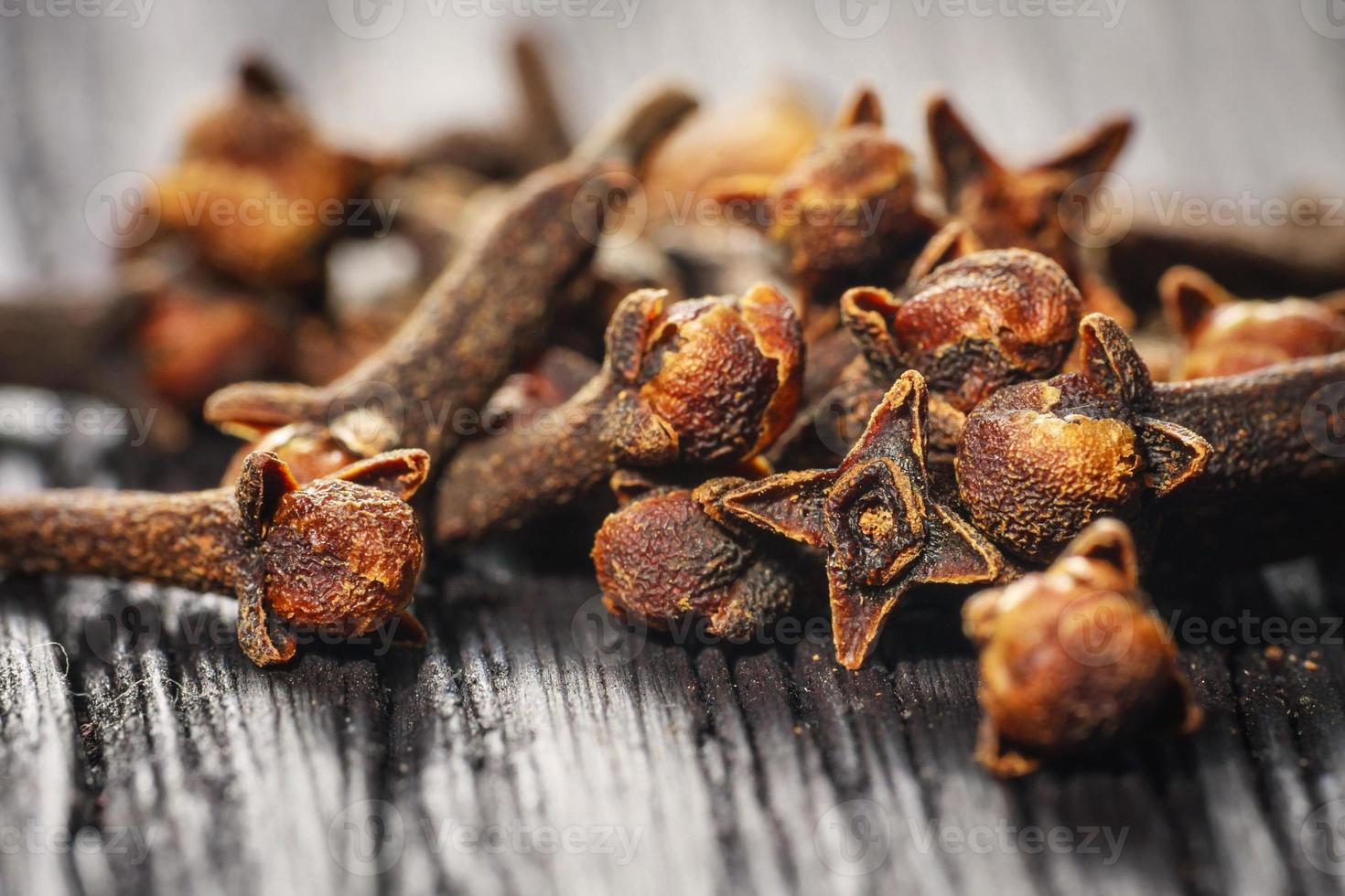 pile cloves on wood background photo